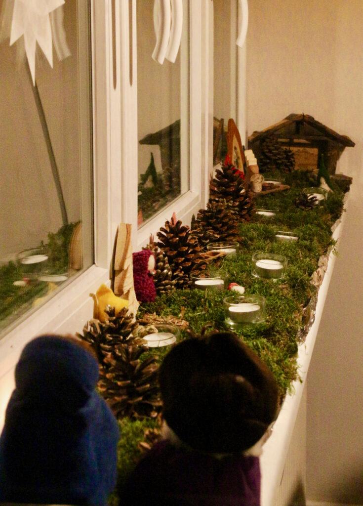 Krippenlandschaft mit Moos auf der Fensterbank, Josef und Maria von hinten am Anfang des Weges