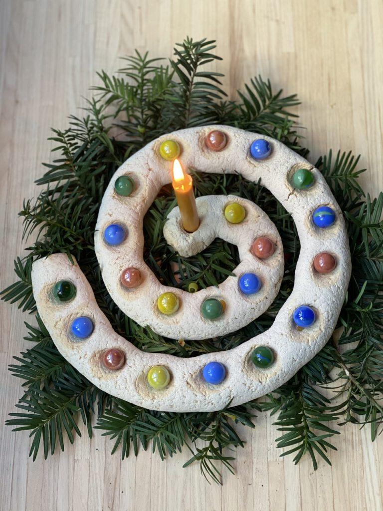 Adventsspirale selber machen: Die Salzteig-Spirale von oben mit der Kerze in der Mitte. Alle Vertiefungen sind mit bunten Murmeln belegt.