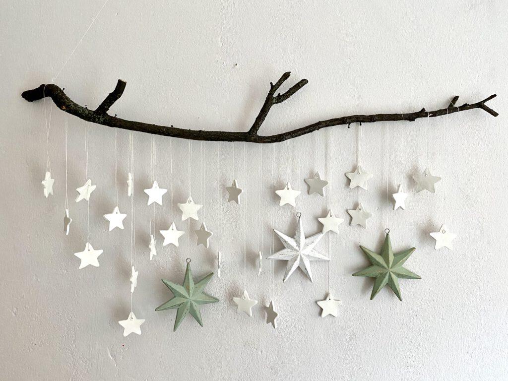 Mobile mit weißen Sternen an schwarzem Stock auf weißer Wand