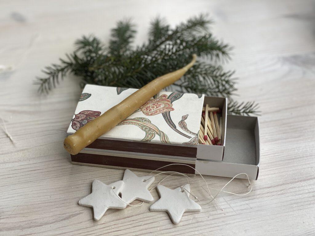 Schnelle DIY Geschenke Idee 2: 2 große Streichholzschachteln aufeinander geklebt, die untere Lade leer, die obere mit Streichhölzern gefüllt. Darauf eine Kerze, daneben kleine Anhänger aus weißer Modelliermasse und ein Tannenzweig.