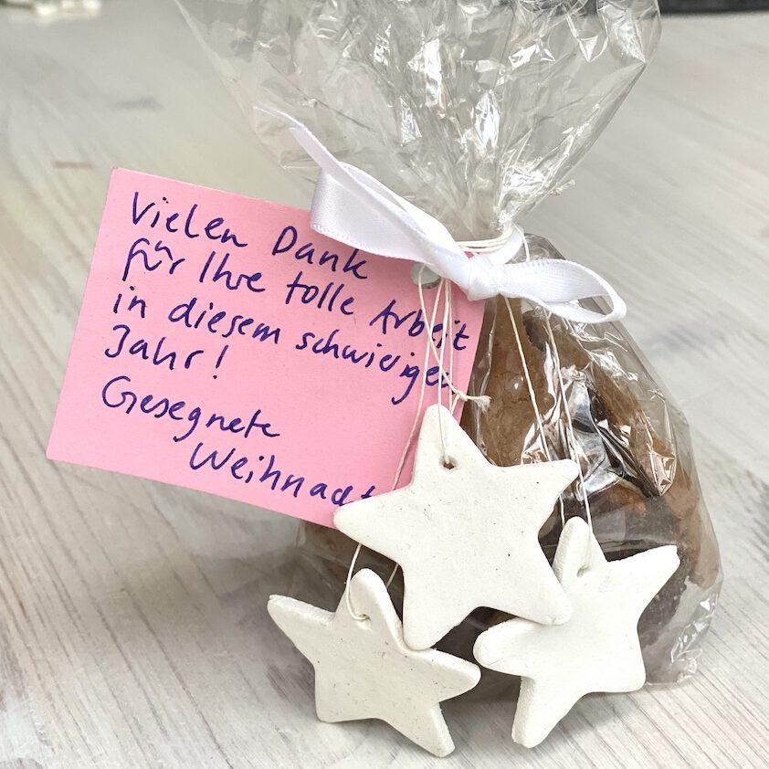 Selbst gebackene Kekse in zellophan-Tüte mit Sternen-Anhängern dran. Außerdem kleine Karte, auf der steht: Vielen dank für Ihre tolle Arbeit in diesem schwierigen Jahr! gesegnete Weihnachten! -- Schnelle DIY Geschenke Idee 6