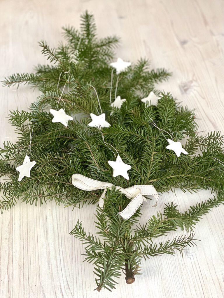 Schnelle DIY Geschenke, 7. Idee: Tannenzweig mit weißen Sternen-Anhängern dran, weiße Schleife drumgebunden.