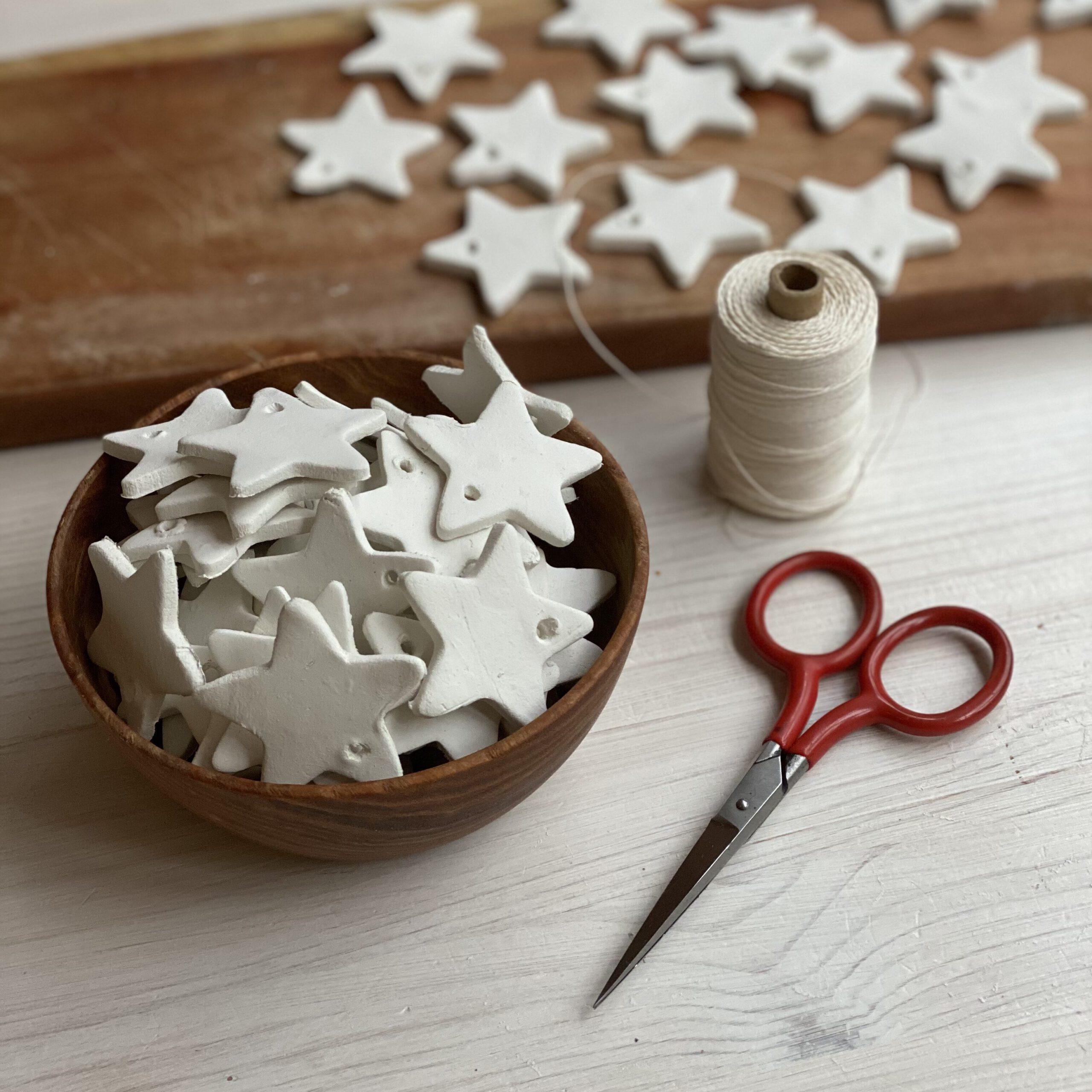 Holz-Schale mit ca. 30 weißen Sternen, rote kleine Schere, Zwirnspule und Brett mit trocknenden Sternen