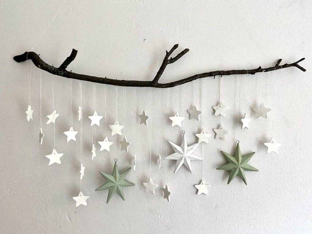 Mobile mit Sternen an einer weißen Wand: Dunkler Stock, an dem kleine weiße und 3 große Sterne mit weißem faden befestigt sind. Die Sterne sind unregelmäßig verteilt.