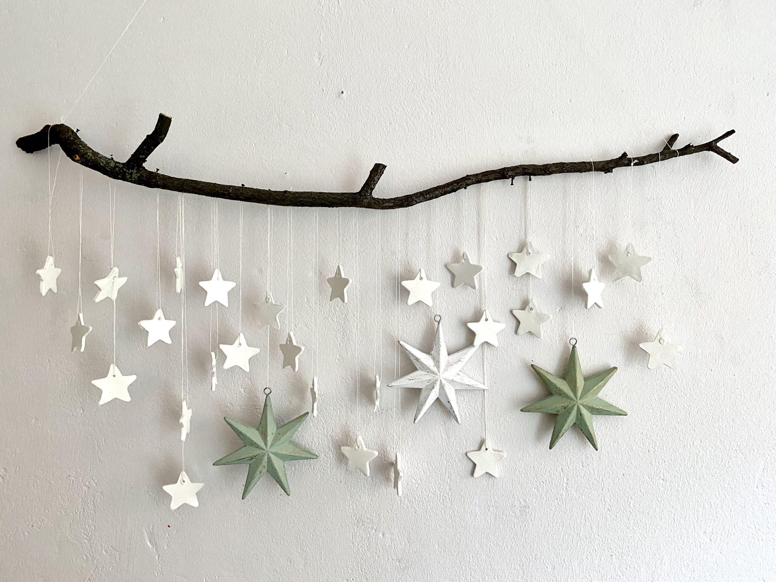 Mobile mit Sternen an einer weißen Wand: Komplettes Mobile mit ca. 25 kleinen weißen und drei großen Sternen in weiß und hellgrün