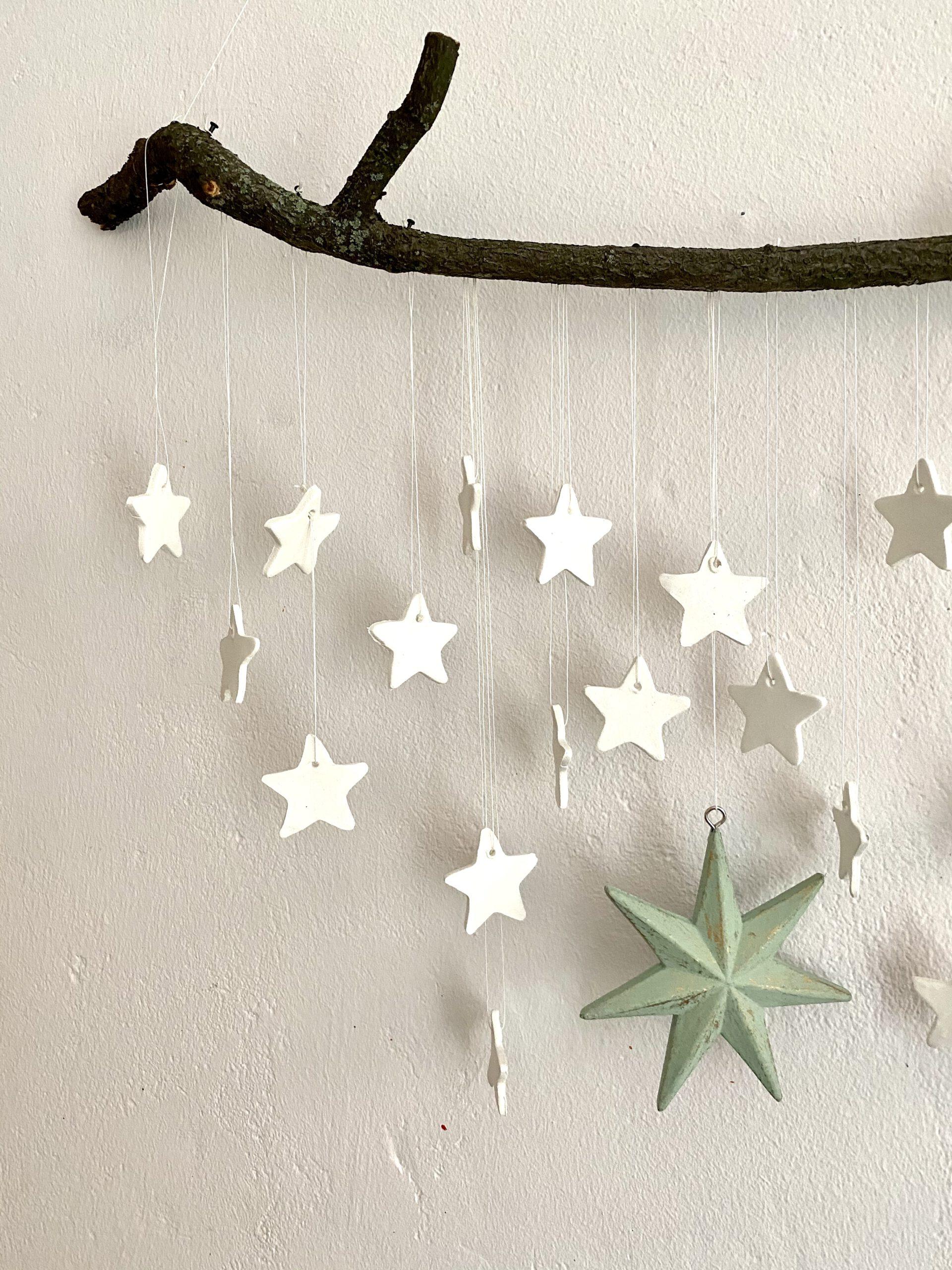 Mobile mit Sternen an einer weißen Wand: Detail mit ca. 15 weißen und 1 großen hellgrünen Stern