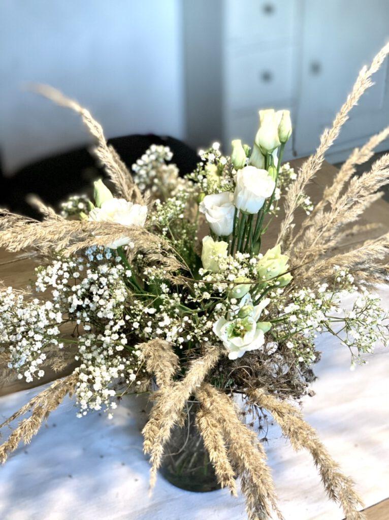 Winterdeko mit Lysianthus, Schleierkraut und trockenen Gräsern auf hellem Holztisch