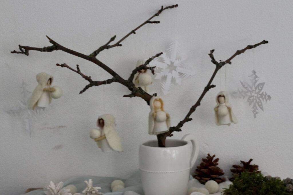 Jahreszeitentisch Puppen Typ Winter / Schneeflockenkinder 5 Stück an kahlem Zweig vor weißer Wand