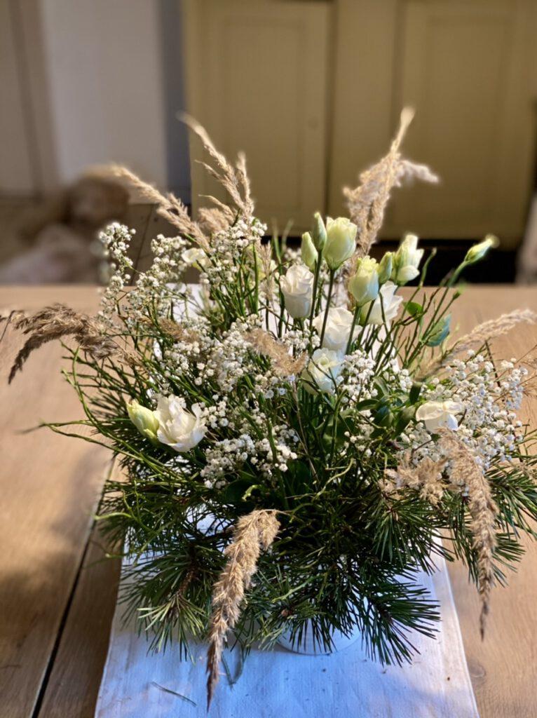 Winterstrauß mit Lysianthus, Blaubeerkraut, Schleierkraut, Kiefernzweigen und Gräsern auf hellem Holztisch
