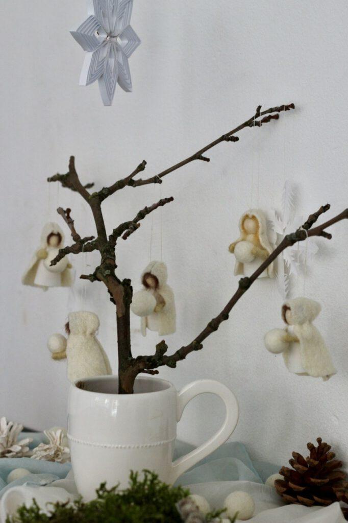 Jahreszeitentisch Puppen (5 Stück) an kahlem Zweig in weißer Tasse, vor weißer Wand