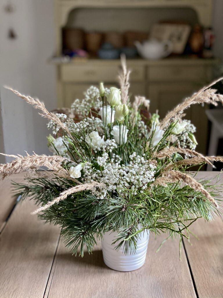 Winterstrauß mit Blaubeerkraut, Schleierkraut, Kiefernzweigen und weißen Blüten auf hellem Holztisch