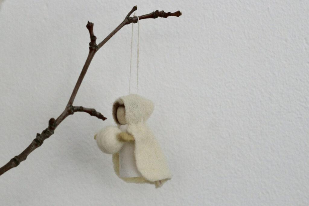 Schneekind mit Schneeball an kahlem Zweig hängend vor weißer Wand