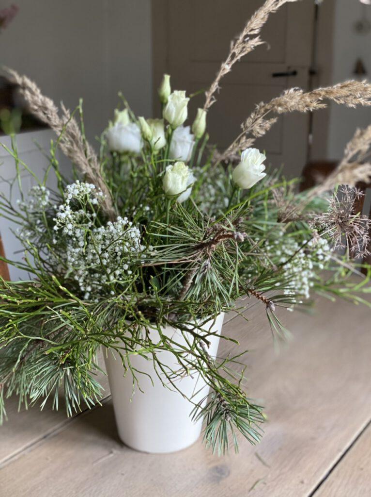 Winterstrauß mit Blaubeerkraut und weißen Blüten auf hellem Holztisch
