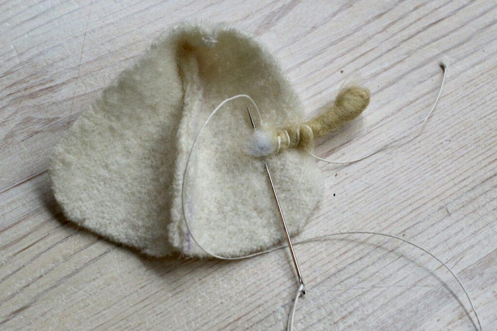 Wie man das Ärmchen im Mäntelchen festnäht.