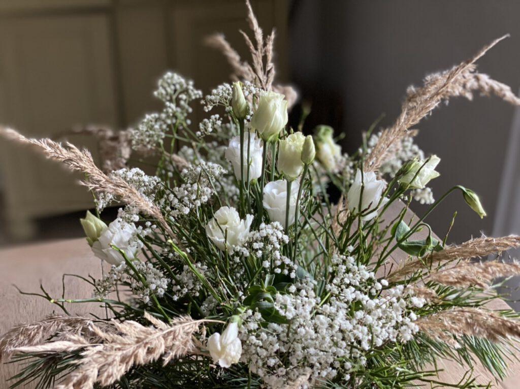 Winterstrauß mit Lysianthus, Schleierkraut und Gräsern auf hellem Holztisch
