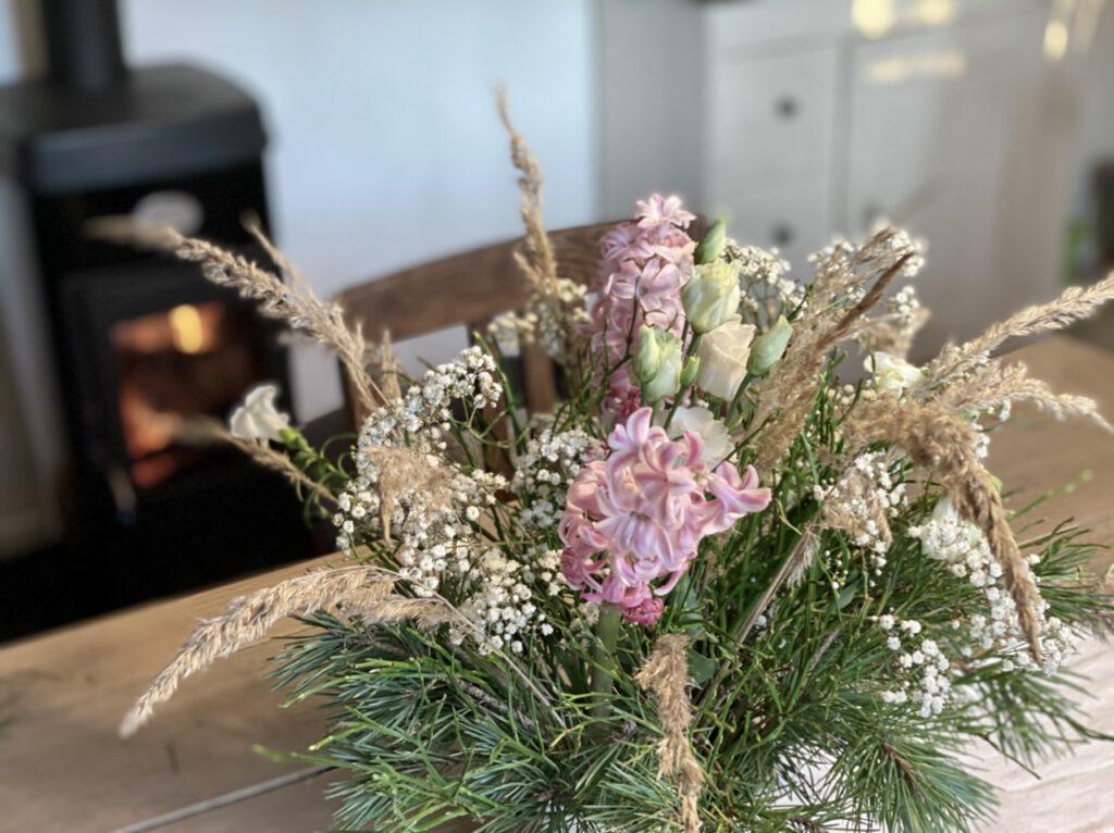 Winterstrauß mit Lysianthus, rosa Hyazinthen, Schleierkraut. Kiefernzweigen und Gräsern auf hellem Holztisch