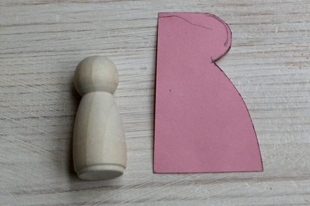 Jahreszeitentisch Puppen selber machen Schritt 1: Rosa Schablone für Mäntelchen neben Holzfigur