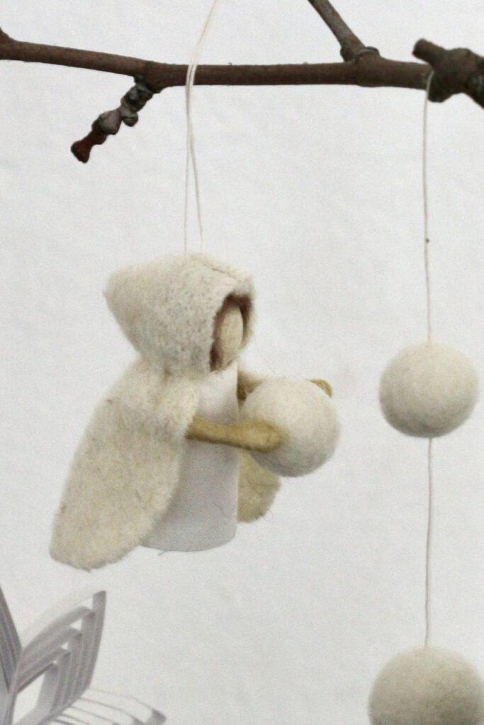 Ein Schneeflockenkind mit Schneeball in den Armen, an Zweig hängend