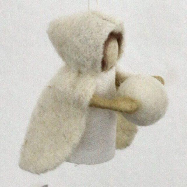 Jahreszeitentisch-Puppe mit Schneeball vor weißer Wand