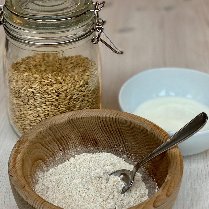 Zutaten für Hafer-Gesichtsaske: Schüssel mit Hafermehl, Joghurt (in Schüssel) und Haferkörner in Glas