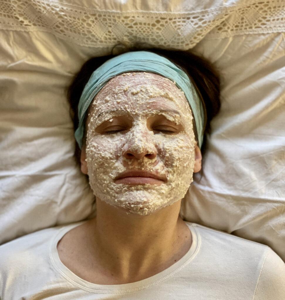 Ich mit entspanntem Gesichtsausdruck mit Hafermaske im Gesicht Kissen liegend