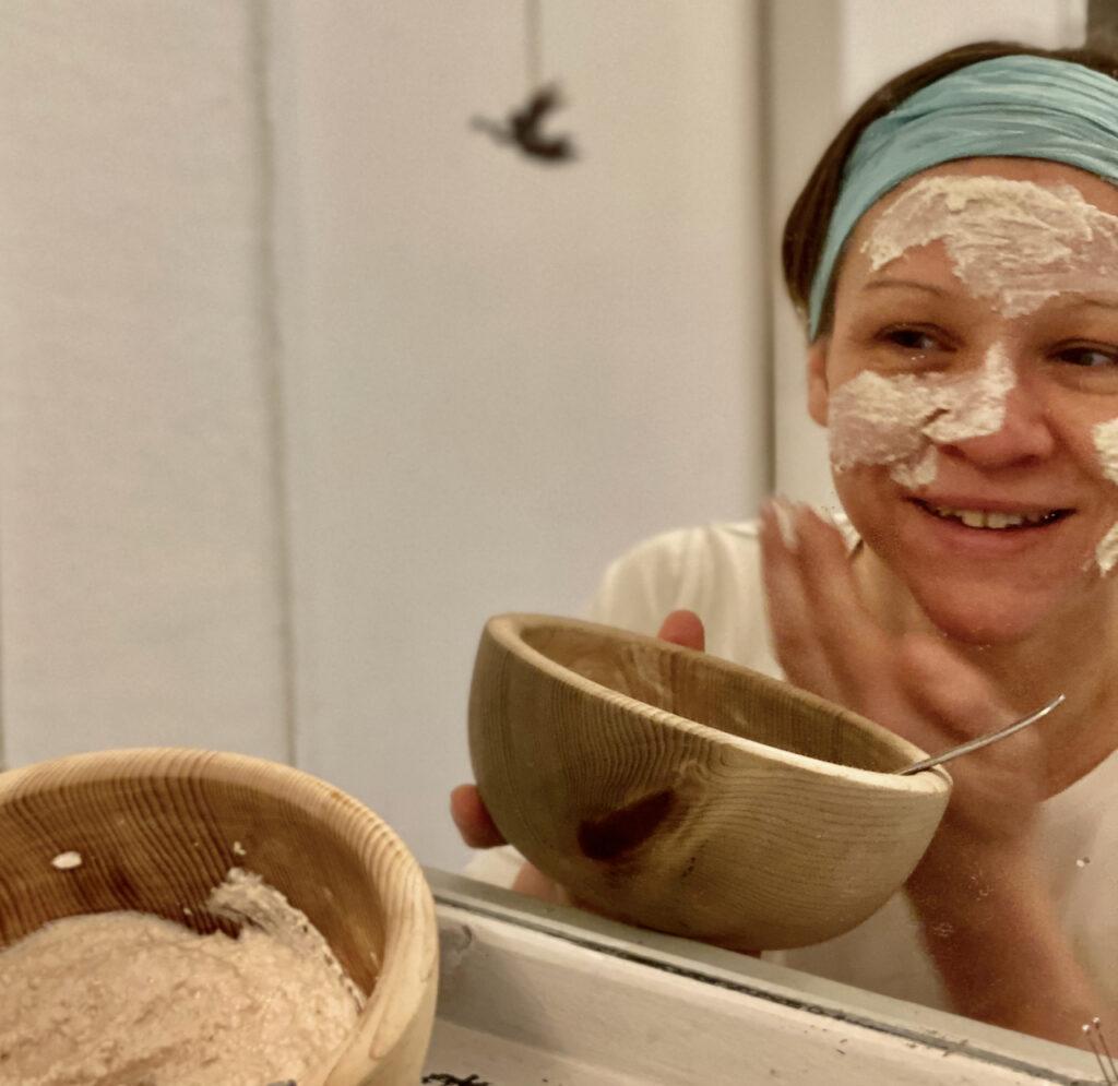Ich lächelnd vor dem Spiegel, wie ich mir die Hafer-Gesichtsmaske aus einem Holz-Schüsselchen auftrage