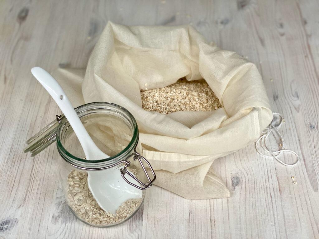 Haferbad: Baumwollbeutel halb mit Haferflocken gefüllt und Glas mit Haferflocken auf weißem Tisch