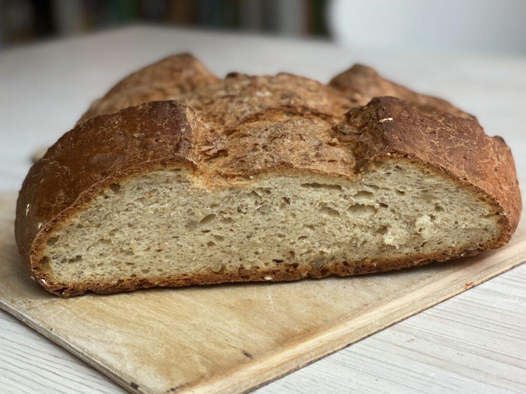 Einfaches Brot backen leicht gemacht: Das Haferflockenbrot mit Quark liegt hier angeschnitten auf einem Brett auf einem weißen Tisch.