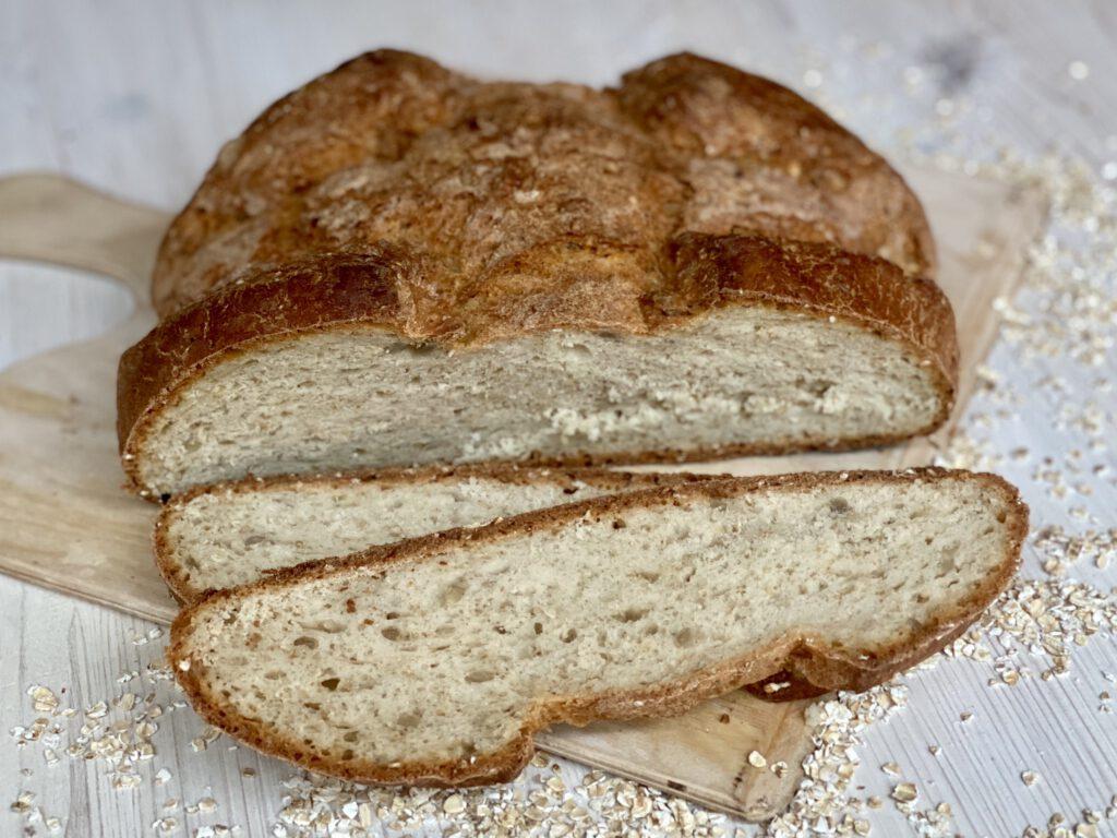 Eingfaches Brot backen leicht gemacht: Das fertige Brot mit zwei Scheiben abgeschnitten auf Brett und weißem Holztisch. Haferflocken auf dem Tisch rund um das Brot.