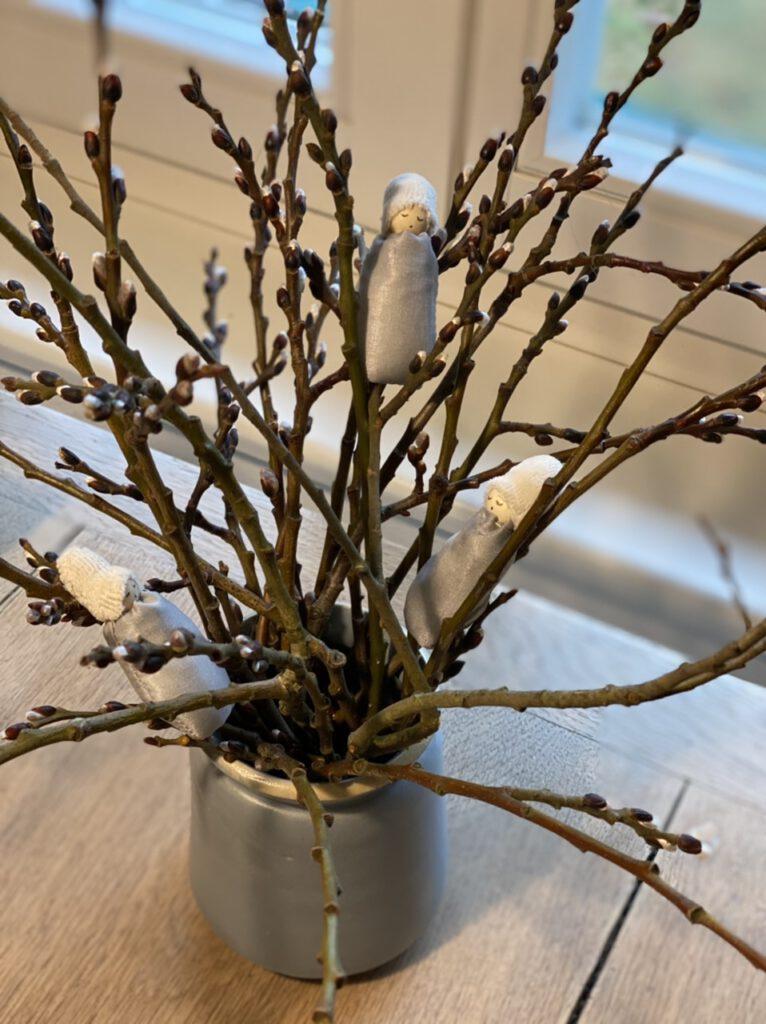 Drei Weidenkätzchen-Blumenkinder in einem kleinen Weidenstrauß auf einem Holztisch, von oben