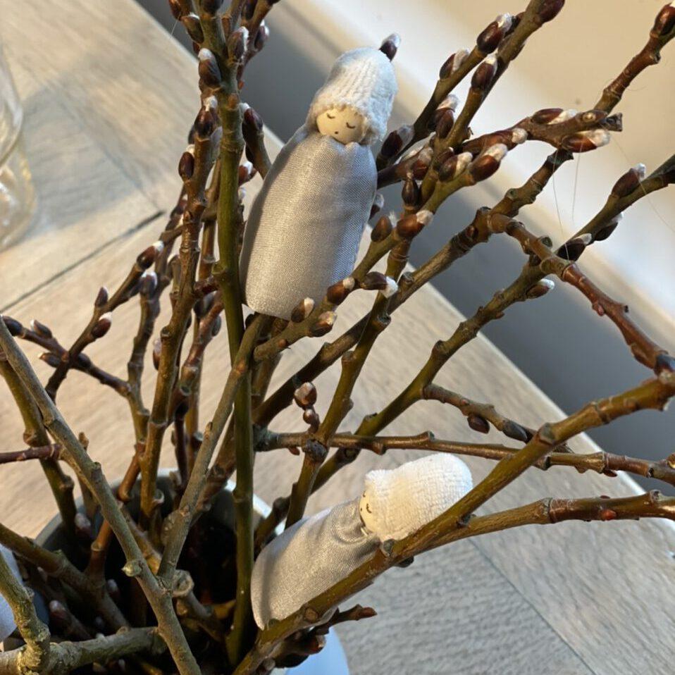 Zwei Weidenkätzchen-Blumenkinder in einem kleinen Weidenstrauß auf einem Holztisch, von oben