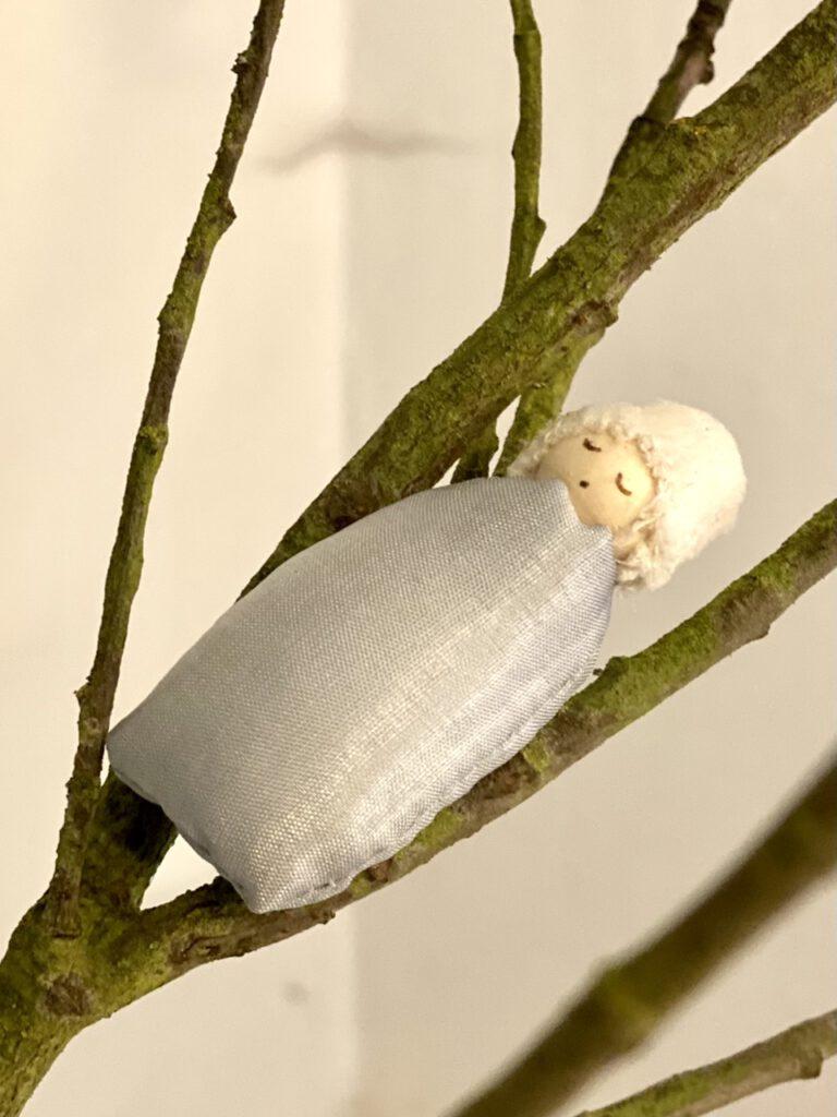 Ein Weidenkätzchen-Blumenkind in einer Astgabel eines Weidenzweigs, liegend