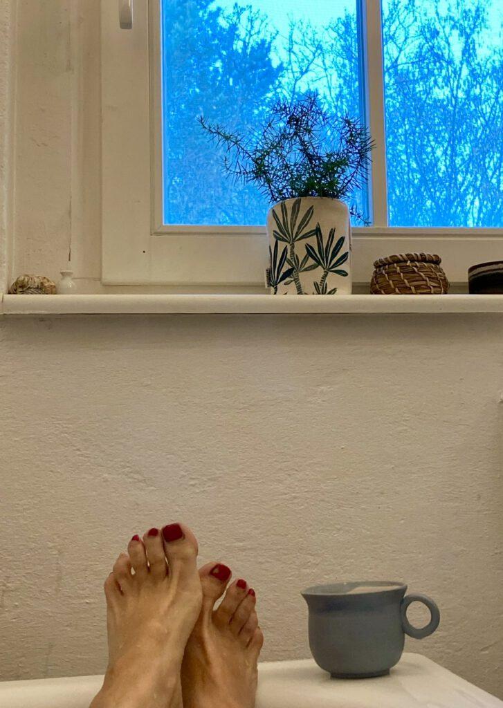 Füße mit rotem Nagellack auf dem Badewannenrand, daneben eine Teetasse, oben ein Fenster mit Wacholderzweigen in kleiner Vase und einem kleinen Körbchen auf dem Fensterbrett.