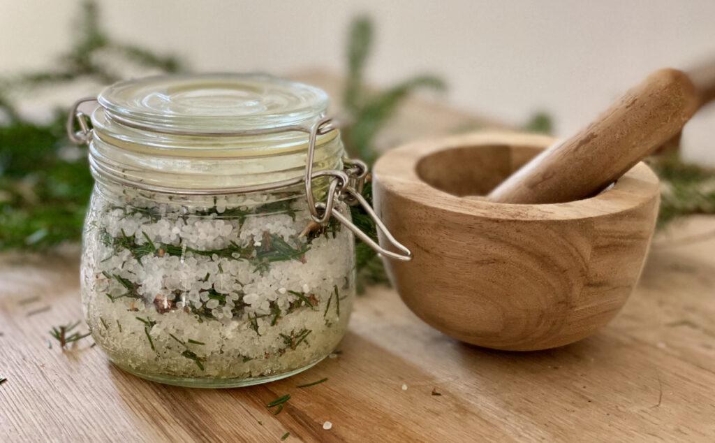 Auf Holztisch ein Bügelglas mit Fichtennadel-Badesalz, Salz und Nadeln in Schichten. Daneben ein Holzmörser. So einfach kann man einen wirksamen Erkältungs- Badezusatz selber machen.
