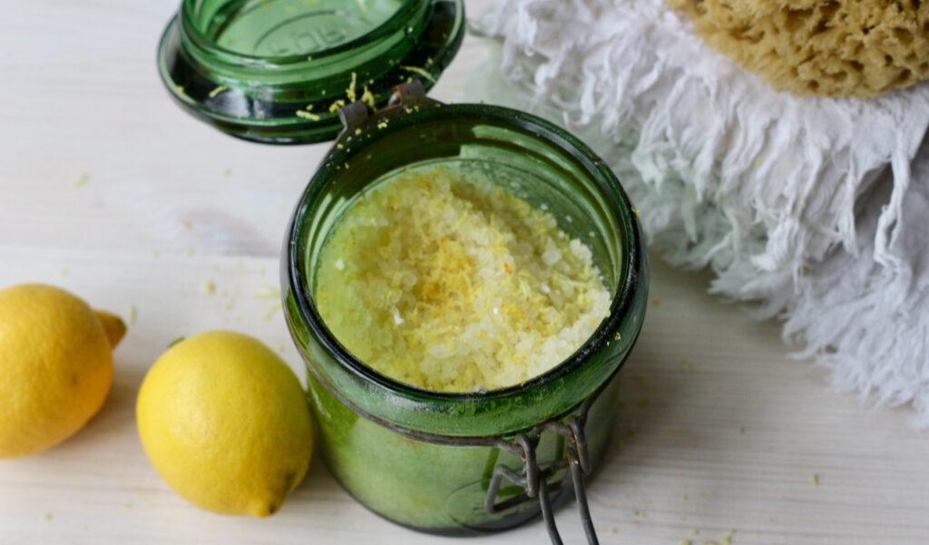 Badezusatz selber machen mit erfrischender Wirkung: Mit Zitrusöl und Zitronenschale. Das Badesalz in einem Glas, auf dem Tisch außerdem 2 Zitronen und ein weißes Handtuch.
