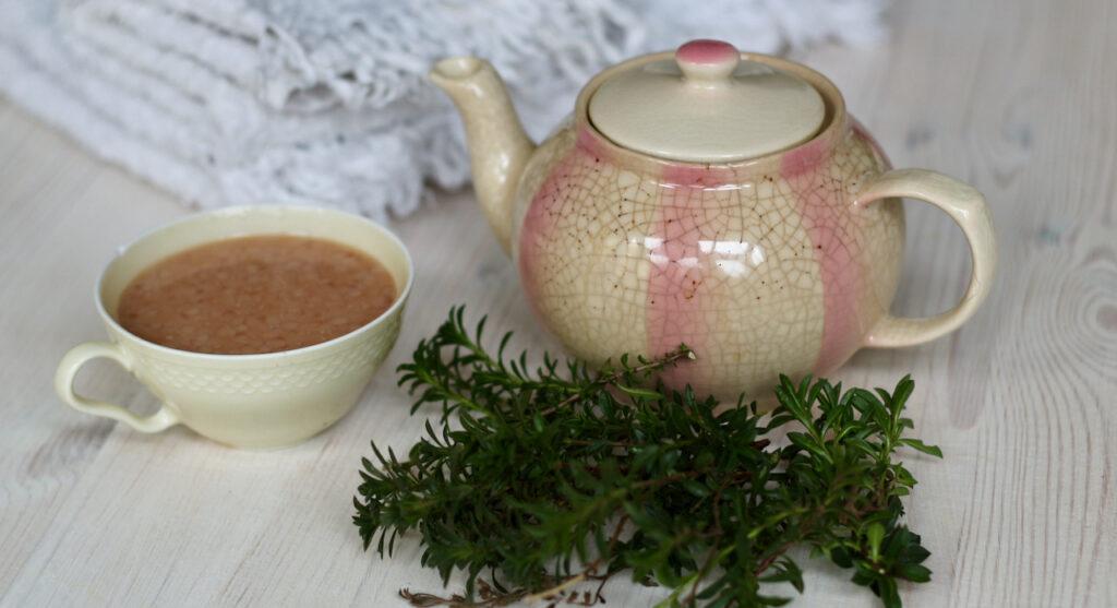 Badezusatz selber machen: Tasse mit Milch-Öl-Mischung und Kanne und ein paar Zweige Thymian, um einen Anti-Depri Badezusatz selber machen