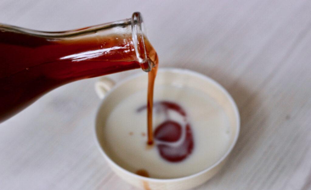 Es wird Johanniskrautöl in ein Schälchen Milch/Sahne gegossen. Das Vermischen des Öls mit Milch oder Sahne hilft beim Badezusatz selber machen.