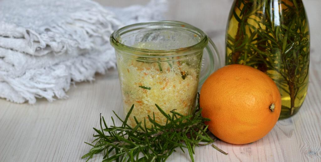 Glas mit kräftigendem Badesalz mit Rosmarin und Blutorange, auf dem Tisch außerdem ein Rosmarinzweig, eine Orange und Rosmarinöl in einer Flasche. Dahinter ein weißes Handtuch. Unten das Rezept für diesen Badezusatz selber machen.
