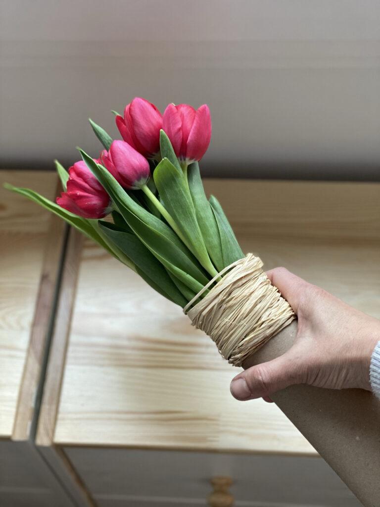 Pinke Tulpen als Geschenk verpackt in der Hand