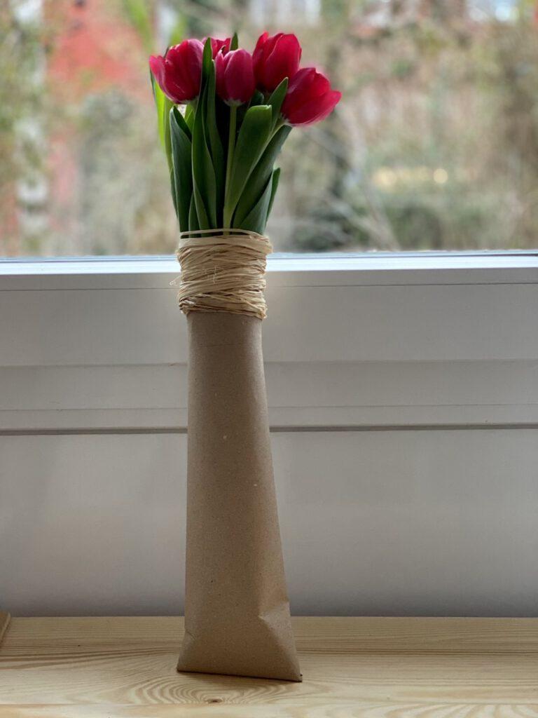 Auch diese pinken Tulpen wurden als Geschenk verpackt - diesmal streng in einer schmalen Pappröhre, die oben einen Kragen aus Bast trägt
