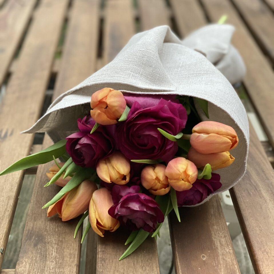Strauß mit orangenen Tulpen und roten Ranunkeln, in Leinen