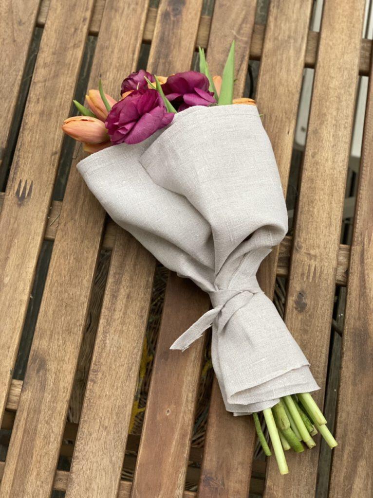 Strauß mit orangenen Tulpen und roten Ranunkeln, umwickelt mit naturfarbenem Leinen, umbunden mit Leinenschleife