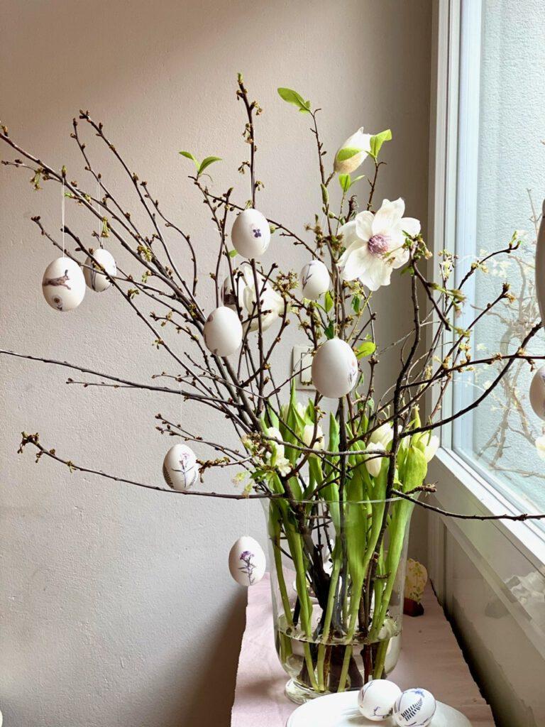 Osterstrauß mit blühenden zweigen und Ostereier mit Blumen verzieren