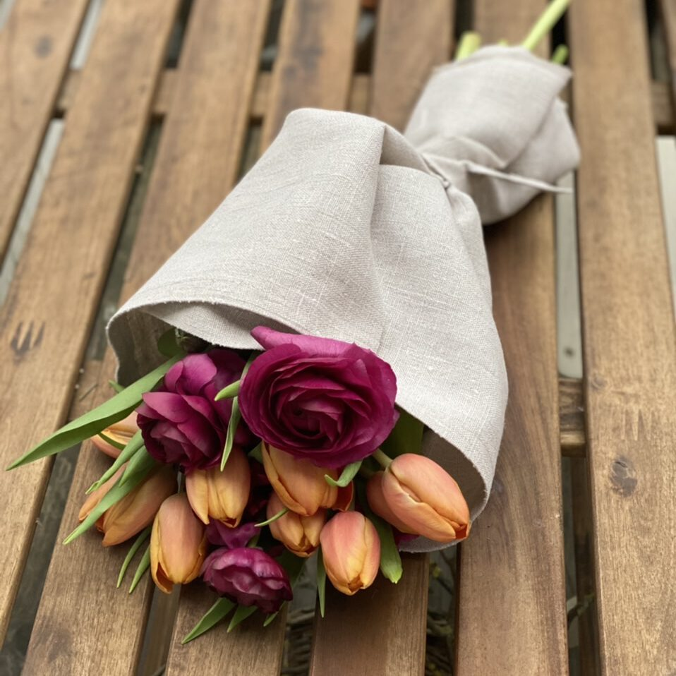 Strauß mit orangenen Tulpen und roten Ranunkeln, umwickelt mit naturfarbenem leinen - so kann man Blumen als Geschenk verpacken.