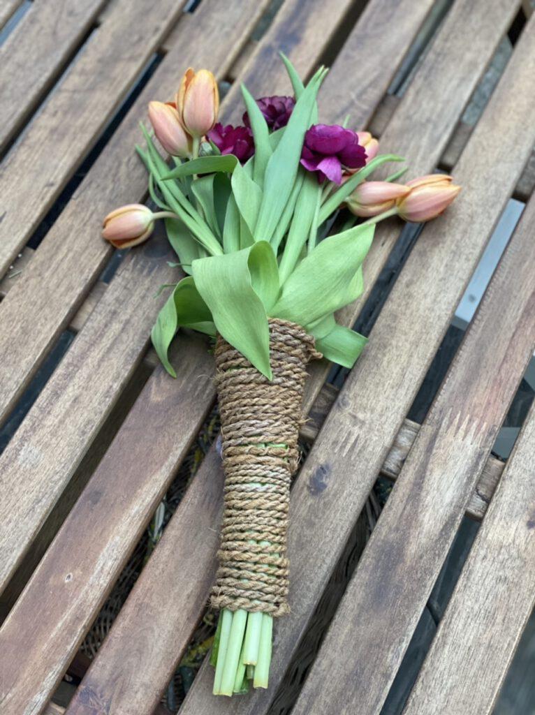 Die Stiele mit grob geflochtenem Seemannsgarn umwickelt: So kann man zarte Tulpen und Ranunkel-Blumen als Geschenk verpacken