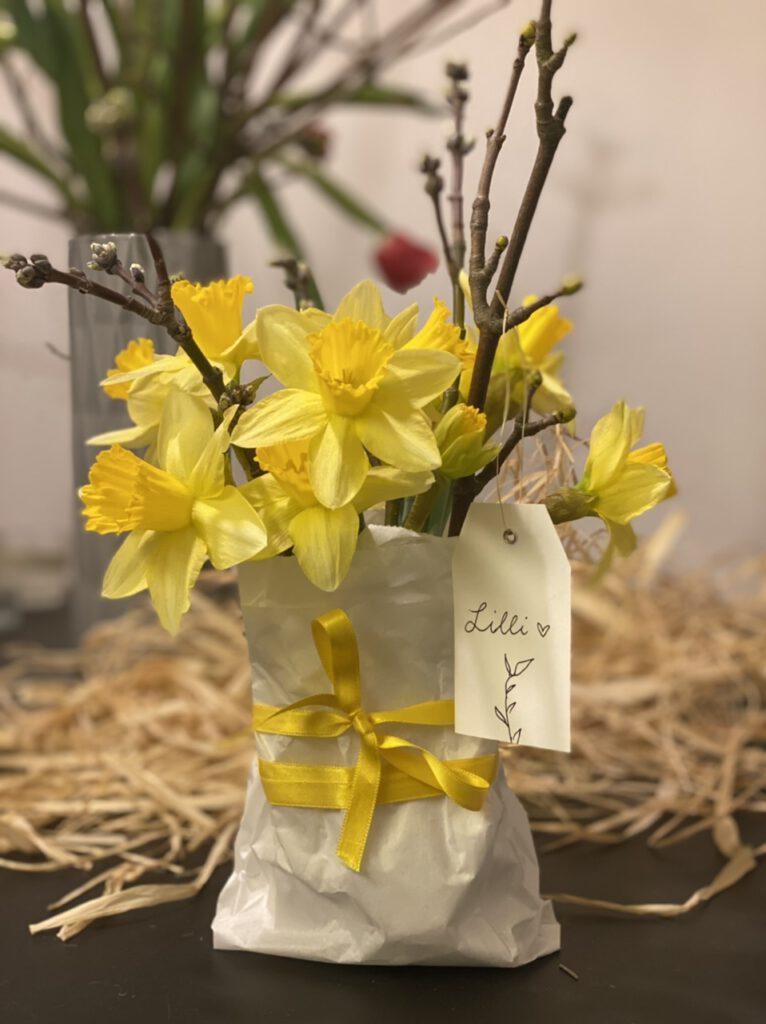 """Auch so kann man Blumen als Geschenk verpacken: Gelbe Narzissen, aufgeblüht, mit Obstbaumzweigen mit Knoten, in Papiertüte stehend, mit langer Schleife aus gelbem Satin und weißem Etikett mit Aufschrift """"Lilli"""""""