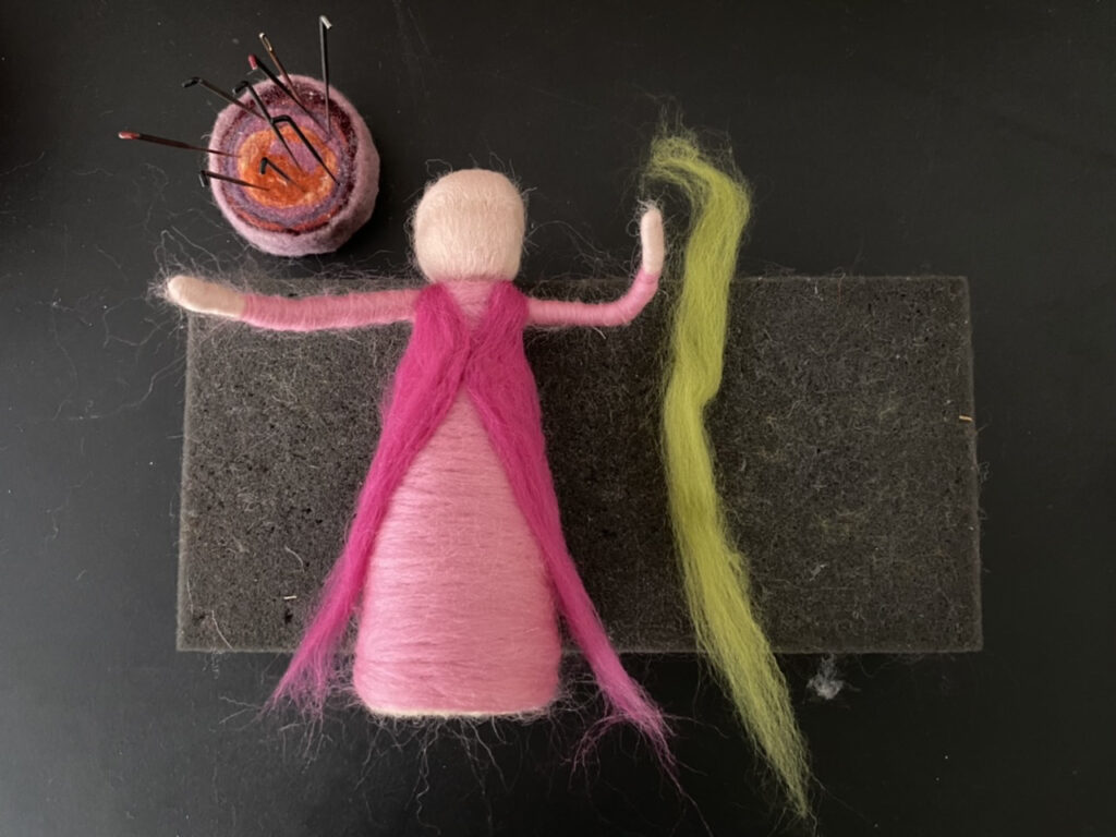 pinker Wollstrang vorne befestigt