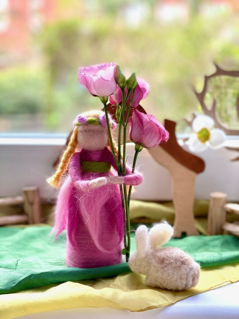 Dieses gefilzte Blumenkind hat eine hellrosa Lysianthus im Arm und einen gefilzten Hasen zu Füßen