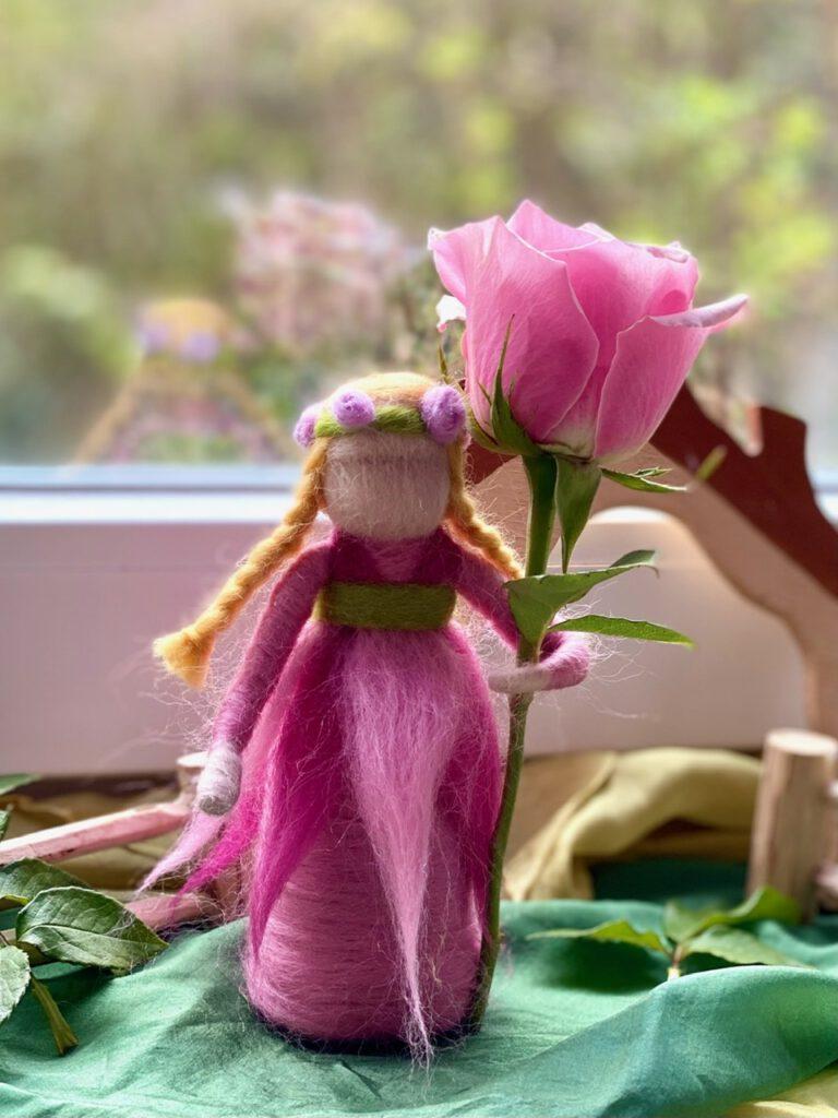 Ein Blumenkind filzen ist nicht schwer - hier das fertige Rosenkind mit einer rosa Rose im Arm