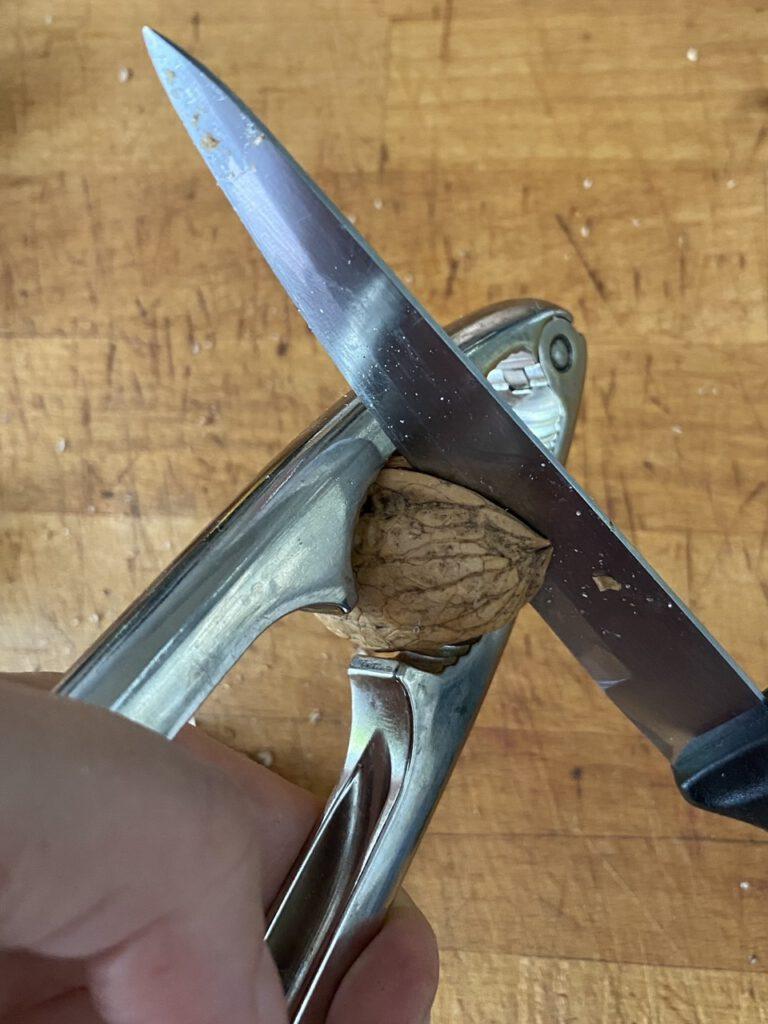 Messer geht in Kerbe von sanft auseinander gedrückter Walnuss